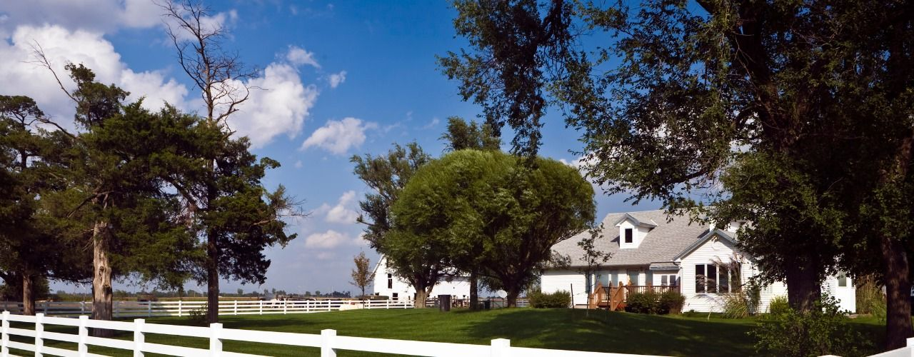 Picture of a white farmhouse with white fence around it